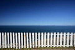 White fence with ocean background. A white picket fence mirrors the blue horizon in the distance royalty free stock photos