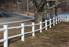 White fence. White post and beam fence leading to the water near a country road Royalty Free Stock Images