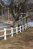 White fence. White post and beam fence leading to the water near a country road Stock Photography