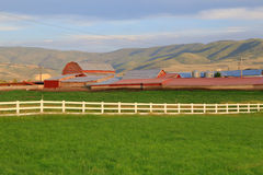 White fence and red barns. Stock Photo