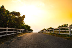 White fence and road side in the evening. Stock Images