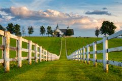 White fence row and barn, Kentucky backroads. A picturesque barn and fence line along one of Kentucky`s scenic byways in the Bluegrass region of the state stock image