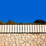 White fence on stone wall Royalty Free Stock Photography