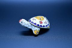 White feng-shui turtle colored metal with detachable carapace shell for jewelry depositing on dark background. A feng-shui white turtle colored metal with stock photo