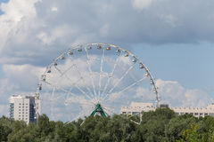 A white ferris wheel against cloudy blue sky front view Stock Image