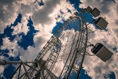 Ferris wheel against cloudy blue sky Stock Photos