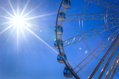 White Ferris wheel with glass light-blue booths against the blue sky and summer sun with bright rays, Helsinki, Finland. Ferris wheel in amusement park in blue Royalty Free Stock Photos