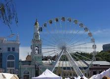 The Ferris wheel at the Kontraktova Square on Podil in Kyiv. White Ferris wheel at Kontraktova Square on Podil in Kyiv against a clear blue sky stock photos