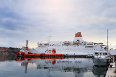 White ferryboat and red tugboats in port Royalty Free Stock Image