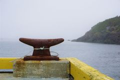 Rusty harbor cleat in foggy Canadian harbor. White fiber knot secures the cast iron metal weight on the dock. Blue still ocean water is in the background. Marine stock image