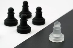 White figure against black figures. one against all. white vs. black stock photo