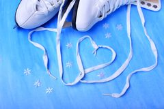 White figure skate shoelaces forming a heart. Against the blue background stock photos