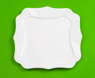 White figured plate on green top view Stock Image