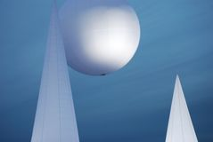 White figures. Abstract white figures against blue sky, cones and sphere Royalty Free Stock Image