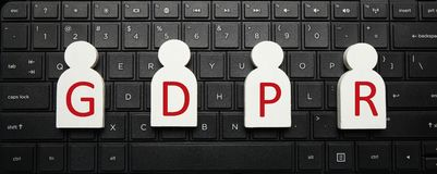 White figures of people on the computer keyboard and the inscription GDPR. General Data Protection Regulation stock image