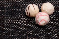 White filled chocolates on a dark cloth Stock Image