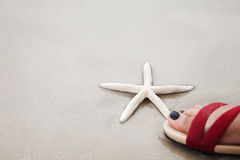 White finger starfish under a human foot over sand beach., Envir Royalty Free Stock Photos