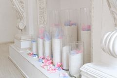 The white fireplace is decorated with candles and flowers stock photos