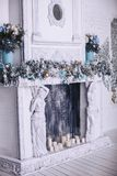 A large beautiful Christmas decorated fireplace in the room. White fireplace decorated for Christmas Stock Photo