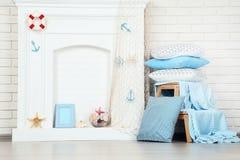 Fireplace with seashells, fishing net. White fireplace with seashells, fishing net and pillows stock photo