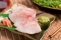 White Fish Sashimi. A delicious white fish sashimi served with wasabi paste, pickled ginger, japanese soy, and seaweed salad Royalty Free Stock Photography