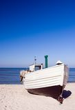 White fishing boat. A white fishing boat standing on the sand of a beach. Clear sky and horizon, nobody in the photo. The Baltic Sea Stock Photos