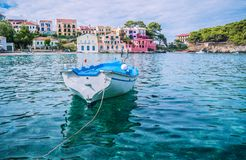 White fishing boat in the blue rippled sea water bay in Assos village, Kefalonia island, Greece.  stock images