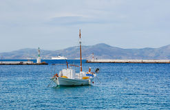 White fishing boat in the blue sea at anchor. Stock Photos