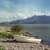 White fishing boat on the coast of Lake Skadar. Montenegro. Film photo. 25 august 2016. stock photos