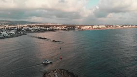 White fishing boat sails from the little city bay at sunset. Drone shot view stock video footage