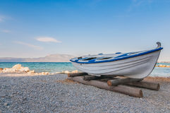White fishing boat on sand with blue sky and water Royalty Free Stock Photos