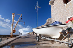 White fishing boat and small crane. Embankment of Petrovac town, Montenegro Stock Photography