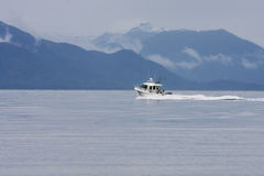 White Fishing Boat Toward Blue Mountains Royalty Free Stock Photography