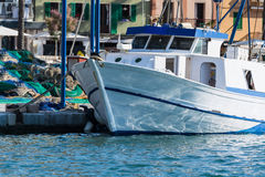 White fishing boat or trawler in the harbor Stock Photos