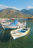 White fishing boats in small mountainous harbour Royalty Free Stock Images