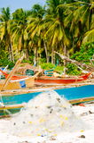 White fishing net on coral sand beach with colorful boats and palms in background Royalty Free Stock Photo