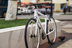 White fixed-gear bicycle on street stock image