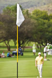 White Flag on Golf Course. A flag pole used to demarcate the current positioning of the hole, on the putting surface [green] of a golf course Stock Image