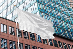 White flag mockup in urban background. White blank flag waving in the wind in the urban background of modern buildings and skyscrapers. Perfect mockup to add any Royalty Free Stock Photos