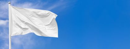 White flag waving in the wind on flagpole against the sky with clouds. On sunny day, banner, closeup royalty free stock image
