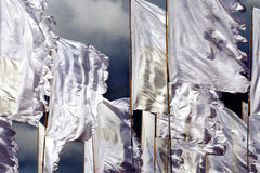 White flags fluttering in wind. Y conditions and a dark cloudy sky above Stock Image