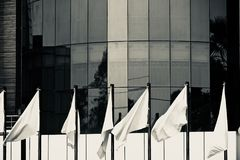 White flags in front of a modern architectural building photograph. The flying white flags in front of a modern architectural building unique stock photograph stock photo