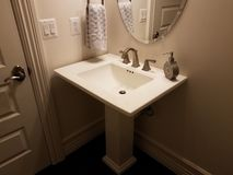 White flat bathroom sink with door and mirror. White flat bathroom sink with hand towel, door, and mirror stock photo