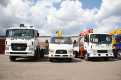 White flatbed trucks with cranes arm is in the parking lot - Russia, Moscow, 30 August 2016 Royalty Free Stock Photography