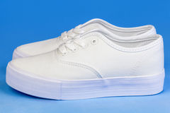 White Flatform Plimsolls on blue Stock Images
