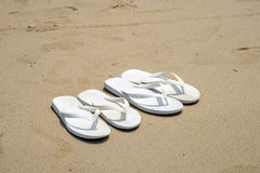 White flip flops on a beach. White flip flops on the beach Royalty Free Stock Images