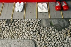 White flip-flops and red clogs Stock Image