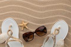 White flip-flops with rhinestones and sunglass, seashell, starfish on the wavy sand. Stock Photo