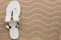 White flip flops with rhinestones on the wavy sand. Royalty Free Stock Image