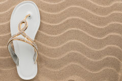 White flip flops with rhinestones on the wavy sand. Royalty Free Stock Photography
